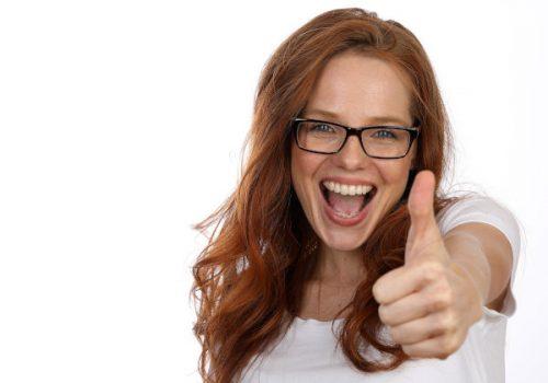 Hübsche rothaarige Frau mit Brille lacht und Daumen hoch