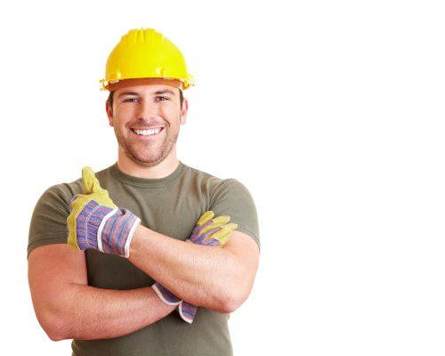 Lachender Bauarbeiter zeigt mit seinem Daumen nach oben